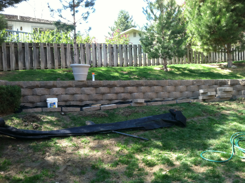 Stone retaining wall along raised area near fence.