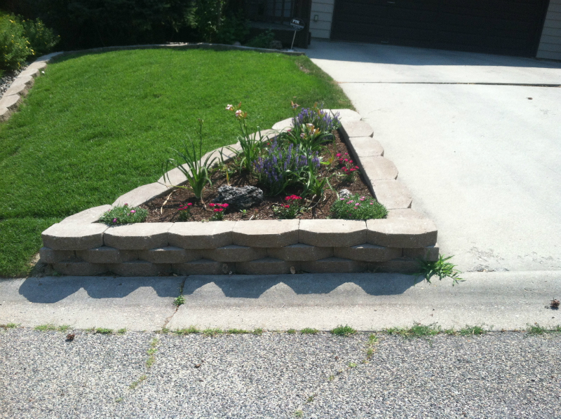 Stone retaining wall creates a beautiful planter next to a driveway.