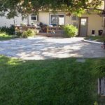 concrete patio in front of house with landscaping
